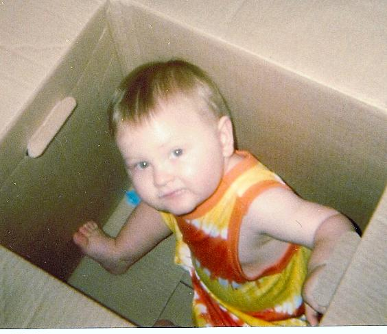 Photo of a young boy in a cardboard box